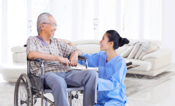 senior man on wheelchair talking to his caregiver