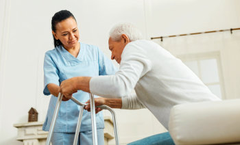 caregiver helping a senior man get up