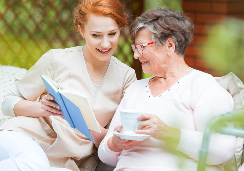 caregiver showing a book to a senior woman