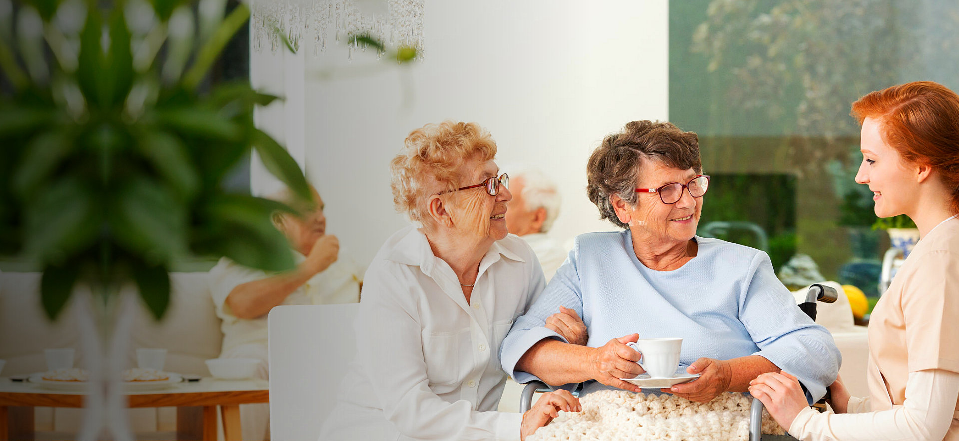 two senior women talking to their caregiver