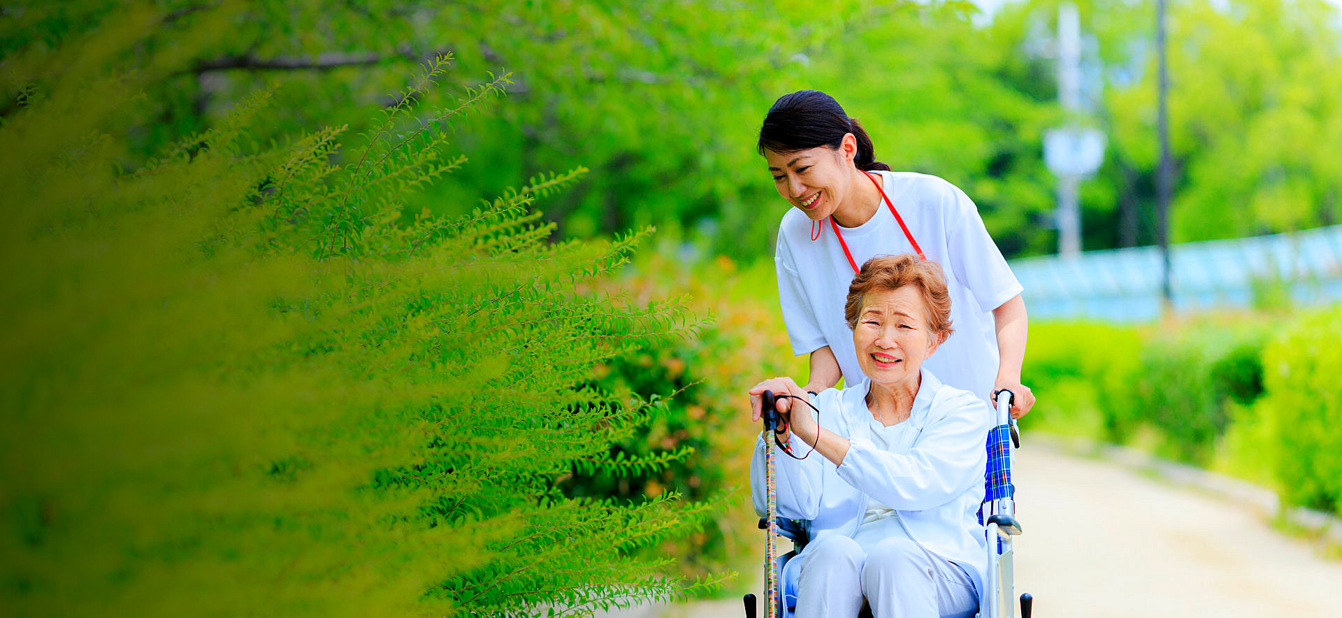 caregiver pushing senior woman's wheelchair on a garden