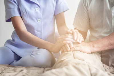 nurse holding senior man's hand