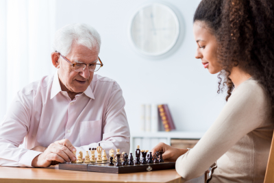 senior man playing chess with private caregiver