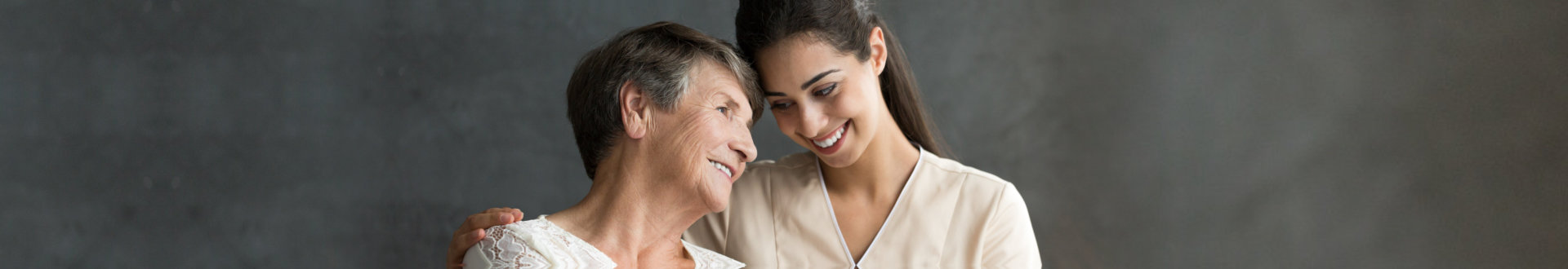 caregiver with senior woman on a dark background